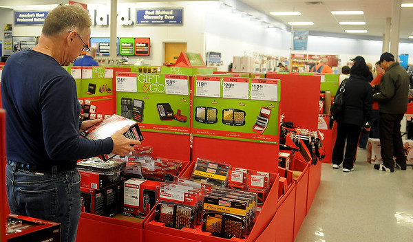 Ken Rapp (left) shops for Craftsman llithium-ion batteries as Black Friday customers wait in line to check out at Sear in Oakwood Mall Friday, Nov. 29, 2013. (Staff Photo by BONNIE VCULEK)