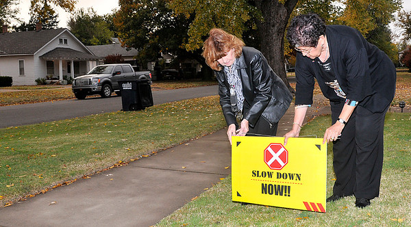 Terri Presa (left) and Tillie Sewell place a sign encouraging motorist to slow down while driving on west Oklahoma street. (Staff Photo by BILLY HEFTON)