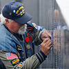 A man makes an etching of a name on the Vietnam Memorial Wall prior to the retirement and dedication ceremony Monday at Woodring Airport. (Staff Photo by BILLY HEFTON)