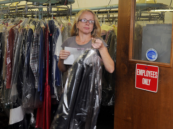 Dawn Whitman delivers dry cleaning to a customer at Oxford Cleaners Thursday, Nov. 21, 2013. The downtown Enid business, owned by Karen Whitley, will close Nov. 29th after opening 75 years ago. (Staff Photo by BONNIE VCULEK)