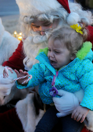 Santa tries to calm a crying child with a candy cane treat during Enid Lights Up the Plains Friday, Nov. 29, 2013. (Staff Photo by BONNIE VCULEK)