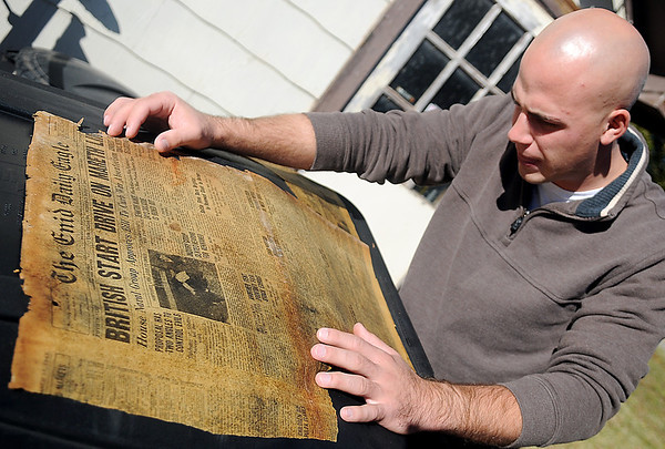 Brian Schwarzlopf examines an edition of The Enid Daily Eagle dated March 17, 1943. Schwarzlopf discovered the old newspaper while removing carpeting and other flooring from his home on N. Taylor. (Staff Photo by BONNIE VCULEK)