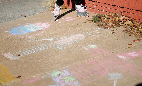 Erin Traynor roller blades across her chalk drawings Saturday, Nov. 30, 2013. (Staff Photo by BONNIE VCULEK)