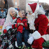 Mrs. Claus listens as Sebastian Cram (center) tells Santa what he wants for Christmas during Enid Lights Up the Plains Friday, Nov. 29, 2013. (Staff Photo by BONNIE VCULEK)