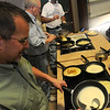 Kevin Ediger (bottom left) pours batter into a hot skillet as Memorial Road Mennonite Brethren Church in Edmond prepare Russian pancakes during the Oklahoma Mennonite Relief Sale at the Chisholm Trail Expo Center Saturday, Nov. 2, 2013. Proceeds from the event provide disaster relief around the world. (Staff Photo by BONNIE VCULEK)