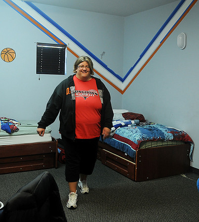 While children are at school, Tennille Chesnut straightens up one of the boys' bedrooms at Thelma J. Gungoll Youth and Family Services Tuesday, Nov. 26, 2013. (Staff Photo by BONNIE VCULEK)