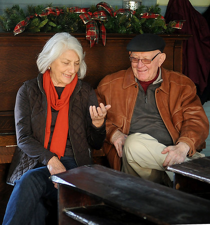 Mary Jane and Jim Gigoux glance at Jim's dog tag as they listen to their sons, daughter-in-law, and five grand daughters share stories about their heritage at the Cherokee Strip Regional Heritage Center's Humphrey Heritage Village Turkey Creek School Tuesday, Nov. 26, 2013. (Staff Photo by BONNIE VCULEK)