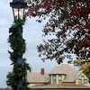 The 1905 Glidewell House, owned by James W. and Alice Glidewell from Helena, looms in the background while Christmas decorations adorn the buildings and lamp posts inside Humphrey Heritage Village Tuesday, Nov. 19, 2013. Tickets are $5 and are now on sale for the community event, Christmas in the Village, sponsored by Humphrey Abstract Company. This holiday favorite will be held on Friday, Dec. 6, 2013, from 5-8 p.m. at the Cherokee Strip Regional Heritage Center's Humphrey Heritage Village. (Staff Photo by BONNIE VCULEK)