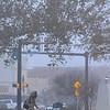 A woman walks through the fog Friday in downtown Enid. (Staff Photo by BILLY HEFTON)