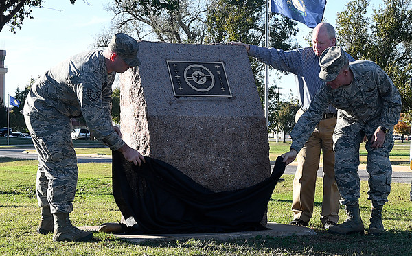 (left to right) Tech Sgt. Anthony Swaim, Dan Ohnessorge and Col. Darrell Judy unveil a plaque comenorating the 75th anniversary of Vance Air Force Base during a Veteran's Day retreat ceremony Thursday November 10, 2016. (Billy Hefton / Enid News & Eagle)
