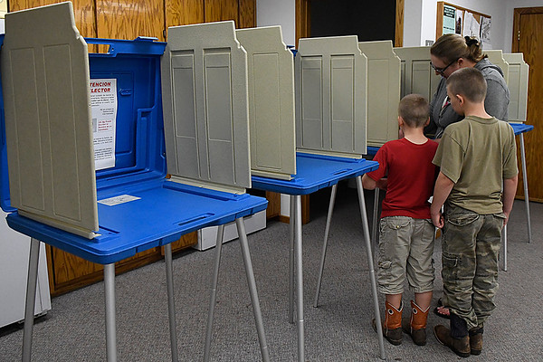 Sara Bullis fills out her election ballot at the Drummond Fire Department as her sons, Haden and Harold, look on Tuesday November 8, 2016. (Billy Hefton / Enid News & Eagle)