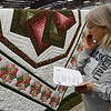 Charleen Williams walks the rows of quilts during the Oklahoma Mennonite Relief Sale Saturday November 5, 2016 at the Garfield County Fairgrounds. (Billy Hefton / Enid News & Eagle)