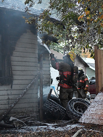 An Enid firefighter sprays foam on a house fire at 1415 E. Maple Monday November 21, 2016. (Billy Hefton / Enid News & Eagle)