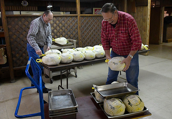 Leroy Patocka and Al Patocka set turkeys in pans at the Knights of Columbus building Friday November 17, 2017. The turkeys will be served during the annual free meal Thanksgiving day 11 a.m. to 1 p.m. at Leven Center at St. Francis Xavier Catholic Church. (Billy Hefton / Enid News & Eagle)