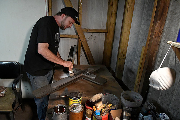 Rodney Fowler puts a clear coat on a cross he made and selling to raise money for missionaries Monday November 13, 2017. (Billy Hefton / Enid News & Eagle)