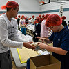 Taye Sullivan (left) hands Max Benge bags of food to pack as part of the Stamping out Starvation project Thursday November 16, 2017. (Billy Hefton / Enid News & Eagle)