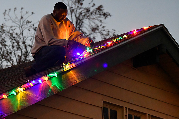 Stacey Robinson hangs Christmas lights at 522 South Johnson Monday November 27, 2017. (Billy Hefton / Enid News & Eagle)
