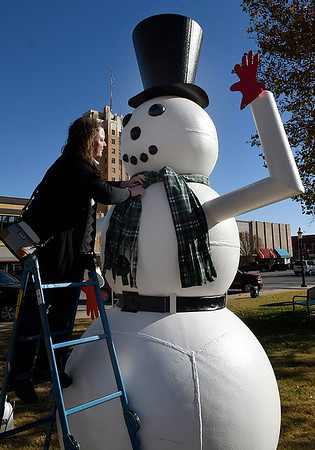 Main Street Enid director, Kelly Tompkins, ties a scarf around the neck of the snowman on the Garfield County Courthouse square Tuesday November 21, 2017. (Billy Hefton / Enid News & Eagle)