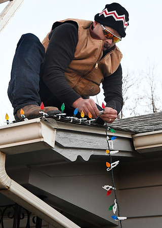 William Cushman hangs Christmas lights on his home on west Oklahoma street Monday November 26, 2018. (Billy Hefton / Enid News & Eagle)