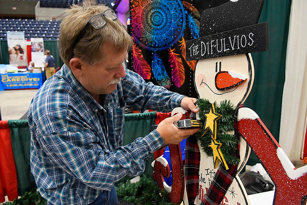 Dennis Crow, from Cyril, Oklahoma, attaches garland to a holiday decoration Saturday November 17, 2018 at the Home for the Holidays Home, Garden, Craft and Gift Show at the Chilsholm Trail Expo Center. The show continues today 11am-5pm. (Billy Hefton / Enid News & Eagle)
