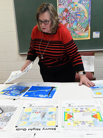 Cathy Moore, Chair Division of Language Arts at NOC Tonkawa, judges entries in Park Avenue Thrift's Starry Night Quilt block coloring contest. The contest was open to Enid Public School 5th graders. Selected entries will be displayed at Park Avenue Thrift beginning December 1. (Billy Hefton/ Enid News & Eagle)
