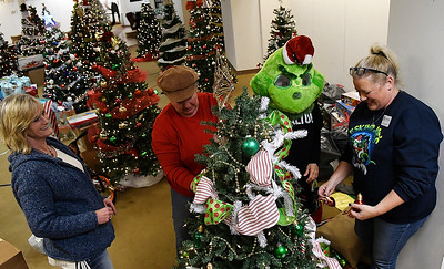 (left to right) Vickie Schroeder, Sondra Hernandez, Tammy Mitch (The Grinch) and Natalie McGee decorate a tree at the Salvation Army Angel Tree store inside Oakwood Mall Friday November 30, 2018. The last day to donate to the Angel Tree program is December 15. (Billy Hefton / Enid News & Eagle)