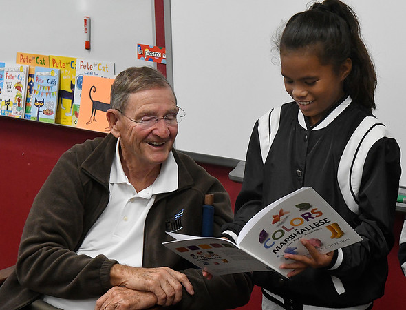 Enid mayor, Bill Shewey, smiles as Jamie Lokkejak reads colors in Marshallese during a meeting of the Marshallese Club at Coolidge Elementary Monday November 5, 2018. (Billy Hefton / Enid News & Eagle)