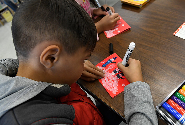 Jordan Buning, a second grader in Mrs. Sue Dell's class at Eisenhower Elementary, makes a Christmas card that will be sent to a school in Peru. (Billy Hefton / Enid News & Eagle)