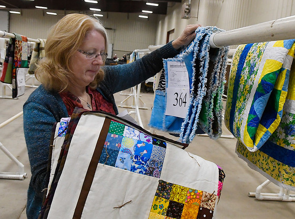 Marlene Barry hangs quilts at the Oklahoma Mennonite Relief Sale at Friday November 2, 2018 the Garfield County Fairgrounds. The sale continues Saturday 7 a.m. - 2 p.m. (Billy Hefton / Enid News & Eagle)