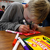 Jayce Garrett, a second grader in Mrs. Sue Dell's class at Eisenhower Elementary, makes a Christmas card that will be sent to a school in Peru. (Billy Hefton / Enid News & Eagle)
