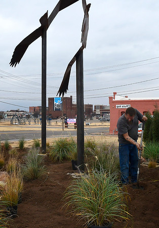 """Jack Rainey plants landscaping grass at the art project """"Lazy Circles in the Sky"""" on the corner of Garriott and Grand Wednesday, November 20, 2019. (Billy Hefton / Enid News & Eagle)"""