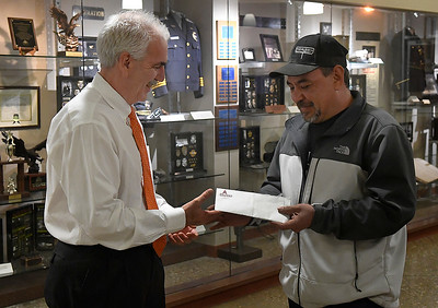 Oscar Ramirez hands Enid police chief, Brian O'Rourke, a donation of cash for officers to distribute to local citizens this holiday season. In 2018 Ramirez was one of the citizens to recieve money from the officers and wanted to show his appreciation by donating cash for officers to hand out this year. (Billy Hefton / Enid News & Eagle)