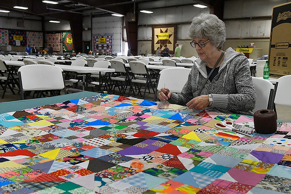 Phyllis Stutzman, from Hydro, Oklahoma, ties a comforter at the Mennonite Relief Sale Friday, November 1, 2019 at the Garfield County Fairgrounds. The Mennonite Central Committee sends comforters around the globe to people in need. Last yeat over 20,000 comforters were sent to Jordan alone. (Billy Hefton / Enid News & Eagle)