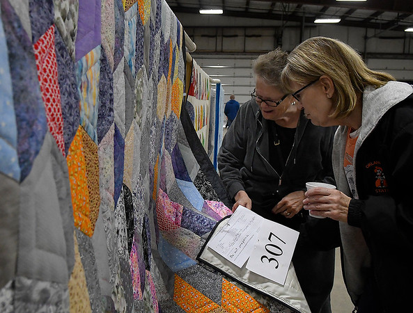 Barbara Fiegel and Denise Ashton looks a quilt for sale at the Mennonite Relief Sale Saturday November 2, 2019 at the Garfield County Fairgrapunds. (Billy Hefton / Enid News & Eagle)