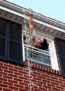 Ron Todd hangs Christmas lights from a second story window at a house on Indian Drive Monday, November 25, 2019. (Billy Hefton / Enid News & Eagle)