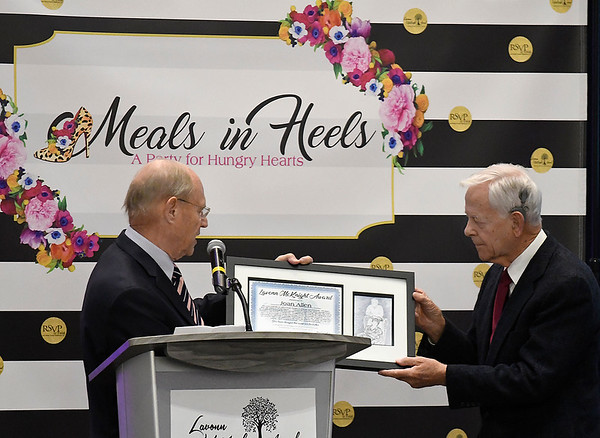 Paul Allen (right) accepts the Lavonn McKnight Award from Dick McKnight on behalf of his late wife, Joan Allen, during the Meals in Heels luncheon Friday, November 1, 2019 at the Stride Bank Center. (Billy Hefton / Enid News & Eagle)