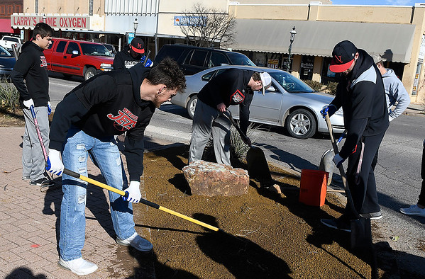 Members of the NOC Enid baseball team spreads decomposed granite ont he corner of Grand and Maine Wednesday, November 13, 2019 as part of the Day of Kindness. (Billy Hefton / Enid News & Eagle)