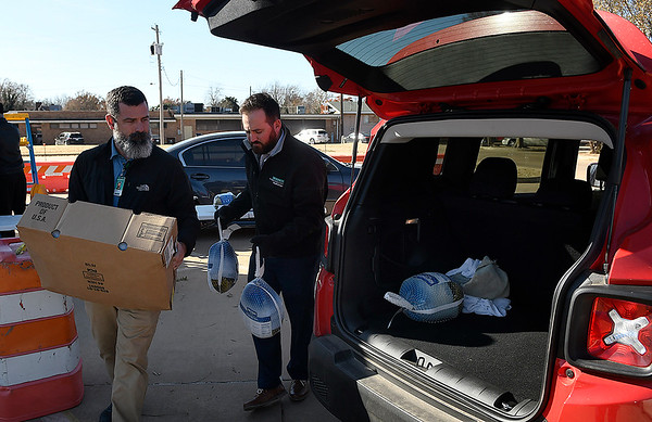 Ryan Royal and Heath Gibson, of Integris Bass Baptist Health Center,  load turkeys into an employee's car Wednesday. November 13, 2019. (Billy Hefton / Enid Nws & Eagle)