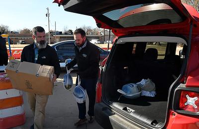 Ryan Royal and Heath Gibson, of Integris Bass Baptist Health Center,  load turkeys into an employee's car Wednesday. November 13, 2019. (Billy Hefton / Enid Nws & Eagle)