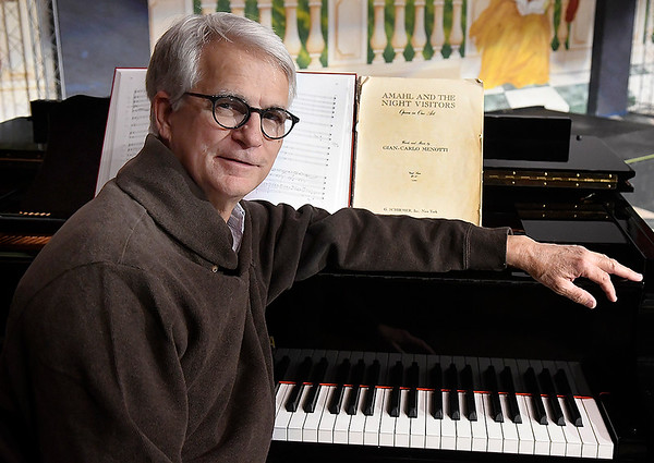 Doug Newell, Enid Symphony Orchestra Music Director, sits a piano with music for Amahl and the Night Visitors that will be performed December 8 at Enid Symphony Hall. (Billy Hefton / Enid News & Eagle)