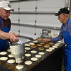 Carl Bartel and Darrell Jantz cook pancakes for the pancake breakfast at the Mennonite Relief Sale Saturday November 2, 2019 at the Garfield County Fairgrapunds. (Billy Hefton / Enid News & Eagle)