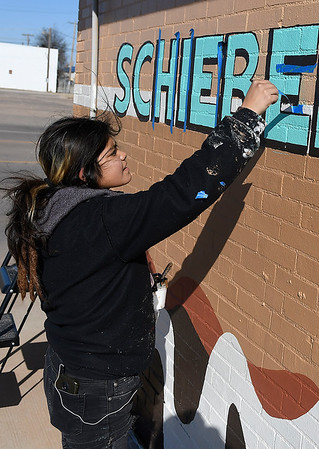 Paulina Capicúa removes tape from a new Schieber's Donuts and Deli logo Thursday, November 14m 2019. (Billy Hefton / Enid News & Eagle)