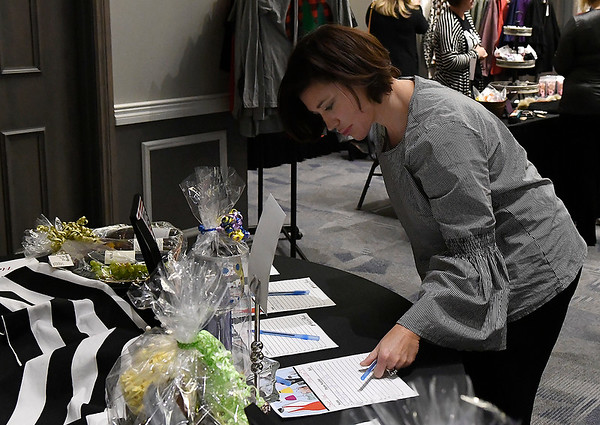 Jamie Moore bids on a silent auction item during the Meals in Heels luncheon Friday, November 1, 2019 at the Stride Bank Center. (Billy Hefton / Enid News & Eagle)