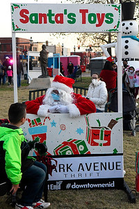 Carlos Magana visits with Santa Claus during Light Up the Plains Friday, November 27, 2020 in downtown Enid. (Billy Hefton / Enid News & Eagle)