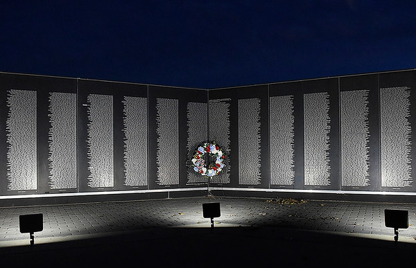 A wreath stands at the Vietnam Memorial Wall at the Woodring Wall of Honor and Veterans Park just after sunset Tuesday, November 10, 2020. (Billy Hefron / Enid News & Eagle)
