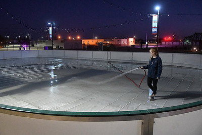 Alexandra Logoutine sprays water to build the ice for the downtwon ice rink Thursday, November 19, 2020. (Billy Hefton / Enid News & Eagle)
