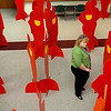A woman stands among the life sized silhouettes of the Silent Witness exhibit Thursday at NWOSU-Enid. The silhouettes represent people who have been killed by domestic violence. (Staff Photo by BILLY HEFTON)