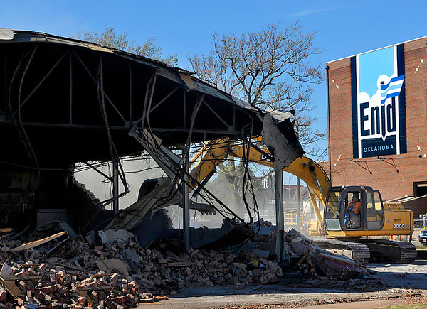 A tract hoe demolishes a building in downtown Enid Wednesday as part of the continuing renaissance project. (Staff Photo by BILLY HEFTON)