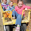 Ashlynn Parker, Chesney Wolever and Madison Wolever ride inside a large wagon at Christ United Methodist Church's Pumpkin Patch Thursday. (Staff Photo by BONNIE VCULEK)