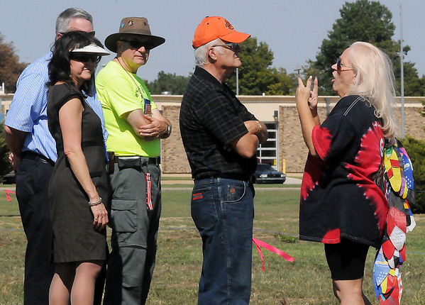 Gayle Woodul, from Marble Falls, Tex., instructs a group of community volunteer judges Tuesday prior to the American Kitefliers Association open individual freestyle competition south of Autry Technology Center. (Staff Photo by BONNIE VCULEK)